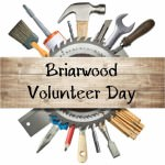 "An unfinished plank for wood with the words ""Briarwood Volunteer Day"" in the foreground; behind the plank is a circular saw and a round array of construction tools."