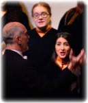 [Image description: cropped photo of a choir. We can see the back of a white man's head, and two white female faces are facing the camera, singing. They are wearing black.]