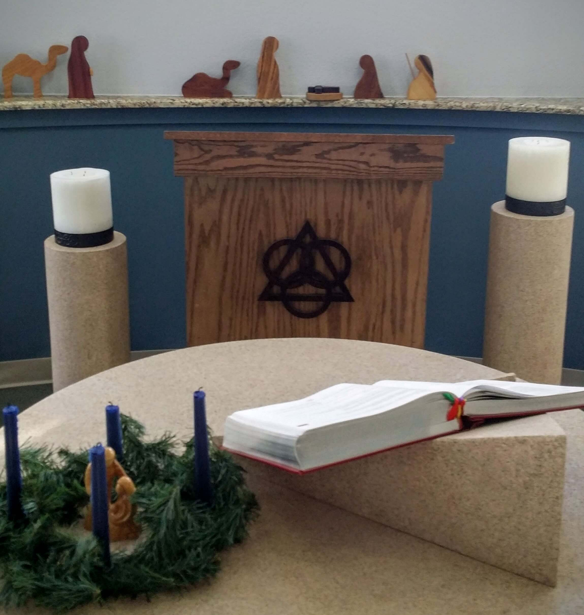 [Image description: photograph of the altar and pulpit of the Anderson Chapel. The Advent wreath is in the bottom left corner of the image. A simple wood nativity set is displayed behind the pulpit.]